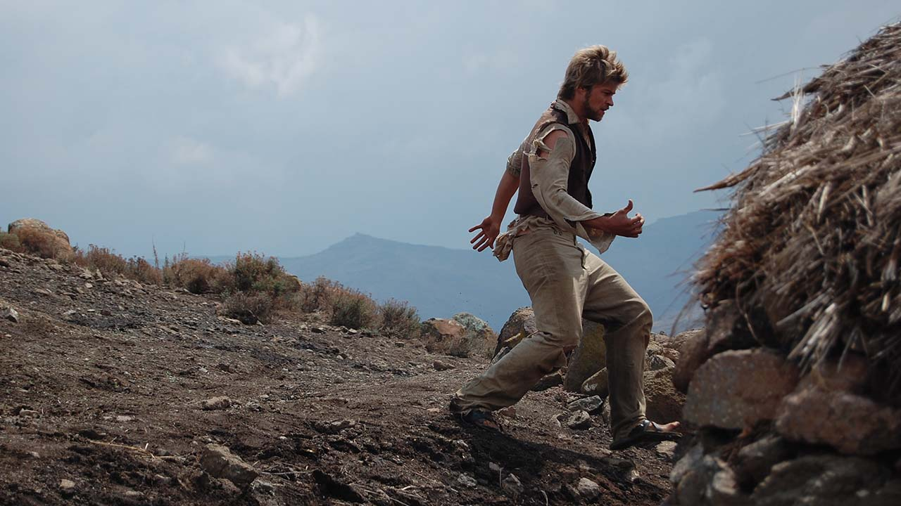 Scene from a film, man in khaki clothes running across planes with mountains in the background