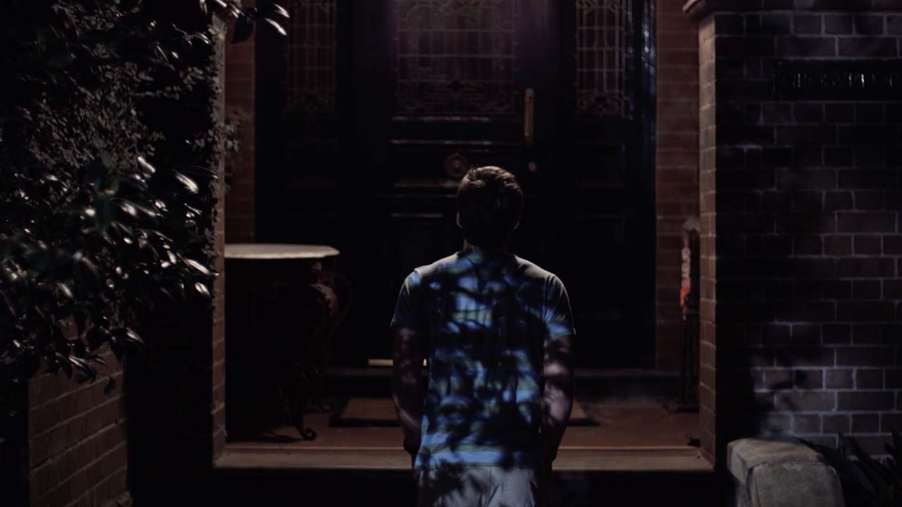scene from a film, man with blue tshirt in front of a front door