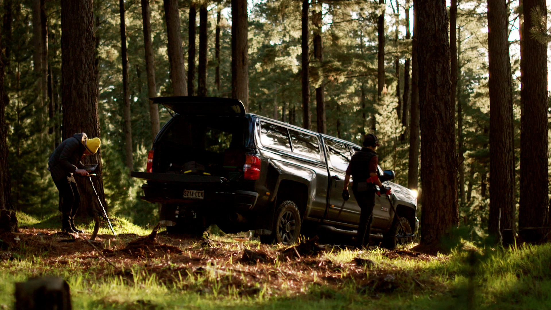 Film Still from the Simply Powerful video. Two men using metal detectors in a forest with an american pick up truck.