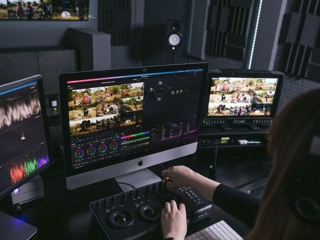 Post production editor sits at desk with 3 monitors editing with a forth large screen on the wall in background.
