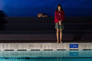 Aquaphobe film image. Girl standing at pool edge with hands clasped.