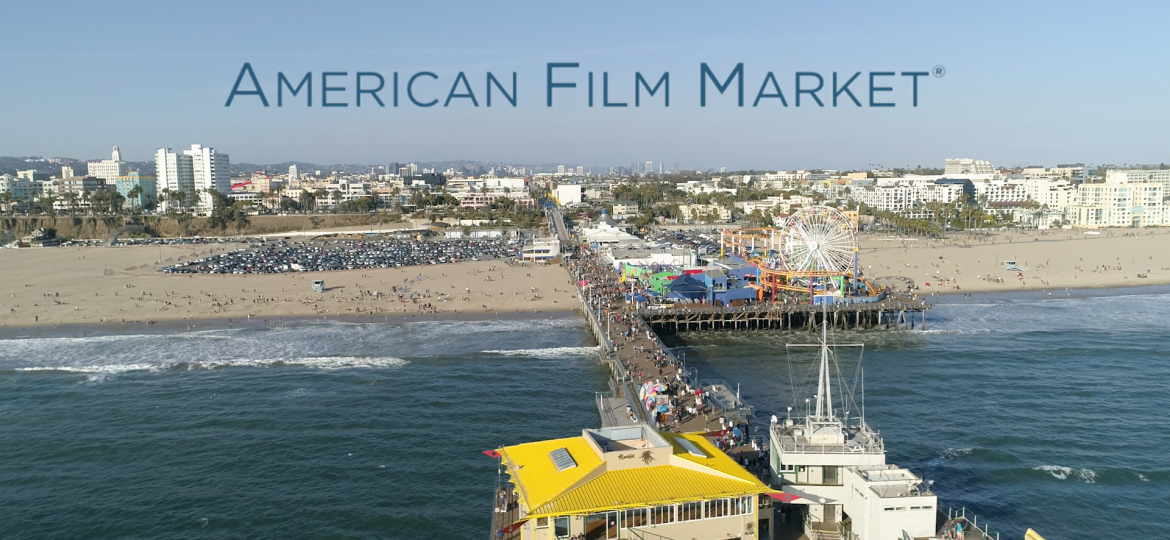 A view of Santa Monica pier, with ocean, then beach with the city in the background. The American Film Market written in blue across the sky.